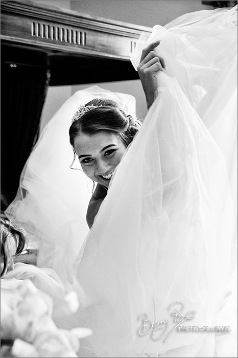 bride peering around dress big smile
