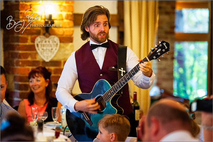 wide eyed singing waiter with guitar