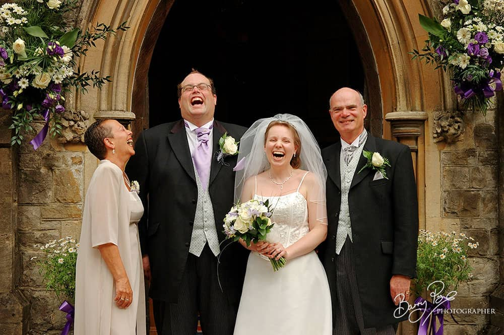 wedding photographer makes group laugh outside kenley church