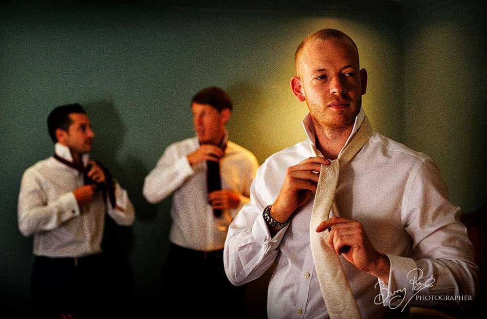 the groom tying his tie