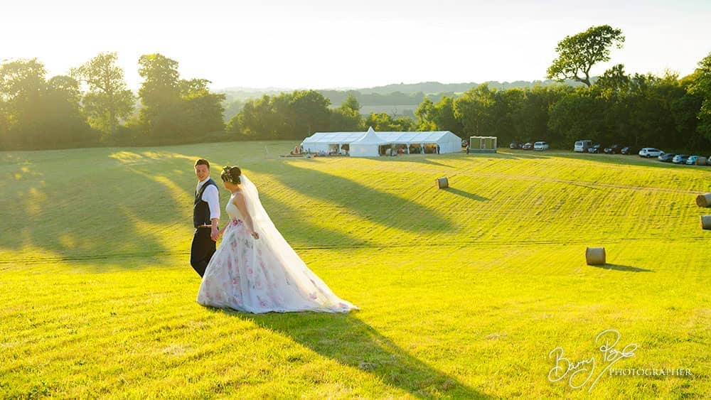 bride and groom walk in sunshine marquee in distance