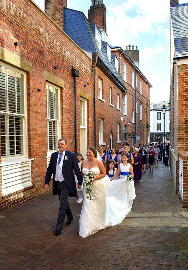 bride and groom and wedding guests walk through tunbridge wells