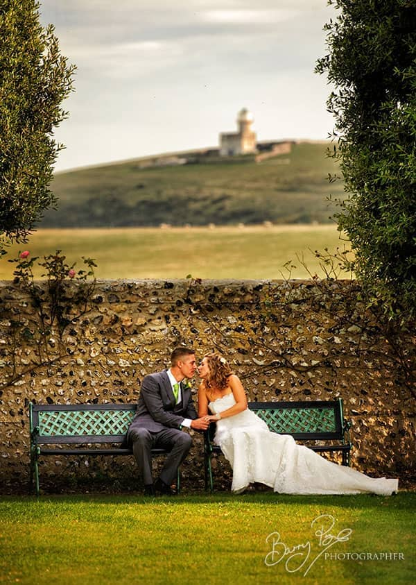 bride and groom in garden birling manor lighthouse in distance