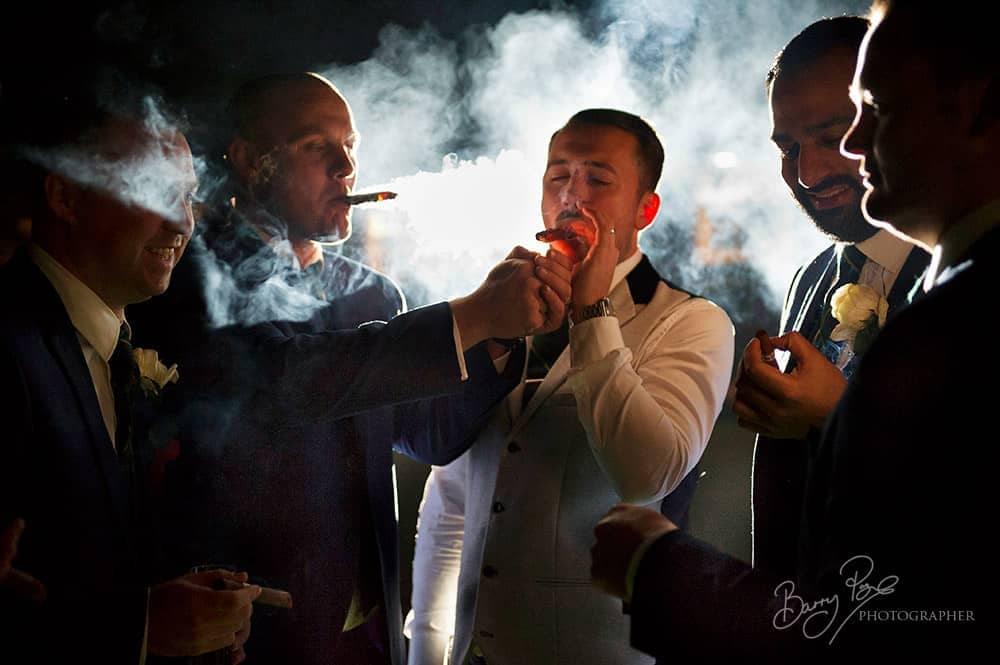 guys with cigar back lit at cooling castle barn