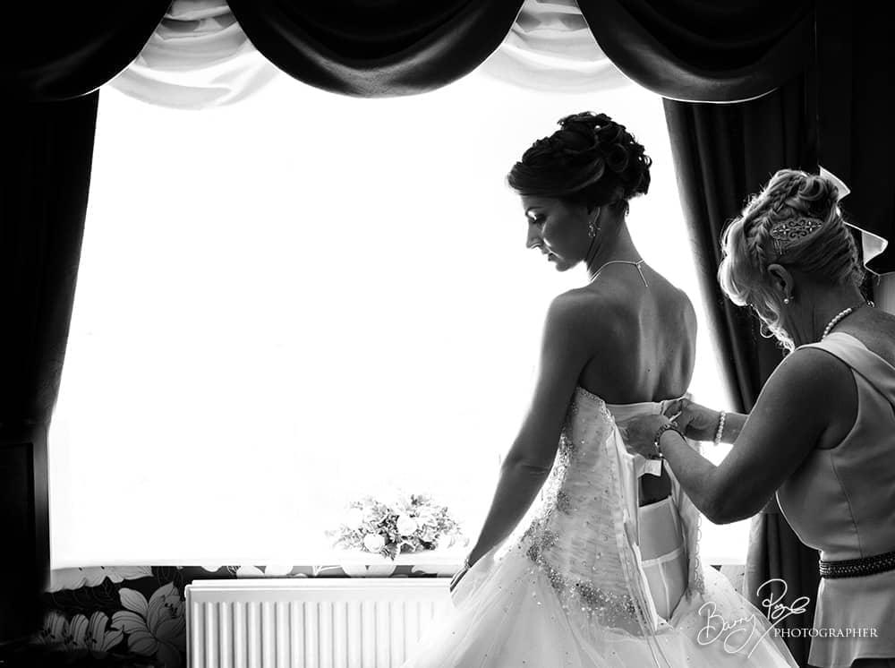 bride getting in dress lit by window