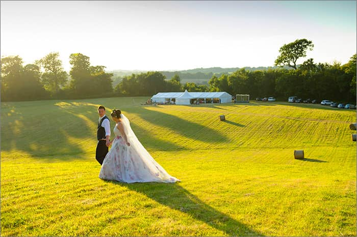 couple in field marquee beyond